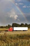 Halb LKW, der unter den Regenbogen fährt Lizenzfreies Stockfoto