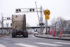 Halb LKW-Traktor, der durch Bahnübergang sich bewegt Stockfoto