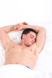 Halb nackter Mann mit beiden Händen oben auf Kissen schlafend im Bett Lizenzfreie Stockfotos