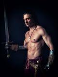 Halb nackter Mann mit einer Klinge in der mittelalterlichen Kleidung lizenzfreie stockbilder