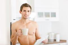 Halb nackter Mann mit Tasse Kaffee liest Zeitung Stockbilder