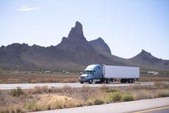 Halb Sattelzugmaschine und Auflieger auf Straße mit Arizona-Berg Lizenzfreie Stockfotografie