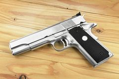 Halbautomatische Pistole auf grauem hölzernem Hintergrund, Pistole 45 lizenzfreie stockfotos