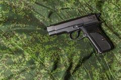 Halbautomatische Pistole auf Pixeltarnungshintergrund Stockbild