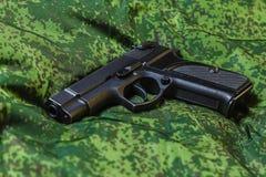 Halbautomatische Pistole auf Pixeltarnungshintergrund Lizenzfreie Stockfotos