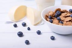 Halbe Ansicht einer nahen Ansicht von Getreide mit Blaubeeren mit moazzarella und Glas Milch auf einem Hintergrund mit zentralem  Stockbilder