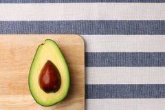 Halbe Avocado auf hölzerner und des Textilhintergrundes Draufsicht stockfotos