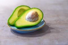 Halbe Avocado mit dem Knochen auf grauem K?che Countertop Platz f?r Text lizenzfreies stockfoto