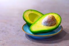Halbe Avocado mit dem Knochen auf grauem K?che Countertop Platz f?r Text lizenzfreie stockbilder