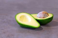 Halbe Avocado mit dem Knochen auf grauem K?che Countertop Platz f?r Text lizenzfreie stockfotos