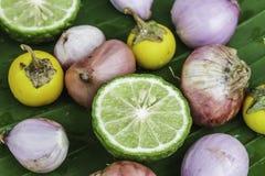 Halbe Bergamottenauberginen und -zwiebeln auf Blattbanane Stockfotos