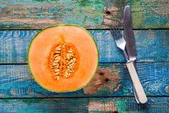 Halbe reife Melone auf einem rustikalen Hintergrund mit Messer und Gabel Lizenzfreie Stockfotografie