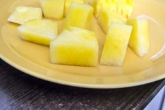 Halbe Scheiben der gelben Wassermelone ohne Knochen auf einer hölzernen Rückseite lizenzfreie stockbilder