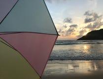 Halbe Szene des Sonnenuntergangs auf Strand mit buntem Pastellregenschirm lizenzfreie stockbilder