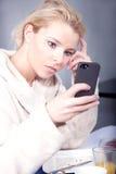 Halbe wache Frau, die ihr Mobile betrachtet Stockfoto