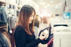Halber Körperschuß einer glücklichen asiatischen jungen Frau mit der Umhängetasche, welche die Kleidung hängt an der Schiene inne stockbilder
