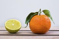 Halber Kalk und ganze Tangerine mit Blättern stockbild