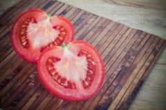 Halber Schnitt der roten Tomate in der Herzform Stockfotografie