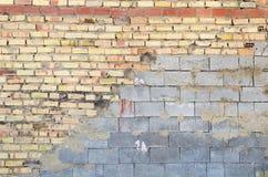 Halber Ziegelstein und halbe Betonmauer Stockbild