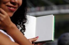 Halbes Foto, Mädchen, das ein offenes Notizbuch hält Lizenzfreies Stockbild