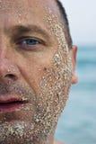 Halbes Gesicht abgedeckt mit Sand Stockfotos