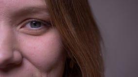 Halbes Gesicht der Nahaufnahme geschossen vom hübschen jungen Mädchen, das in Kamerabrüche in ein glückliches Lächeln aufpasst stock video