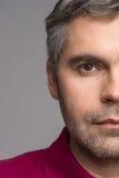 Halbes Gesicht des erwachsenen Mannes auf grauem Hintergrund Stockfotografie