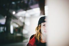 Halbes Gesicht des modischen reizend Mädchens in der roten Jacke, die stilvolle Kappe trägt lizenzfreie stockbilder