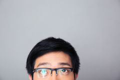 Halbes Gesichtsporträt des asiatischen Mannes oben betrachtend copyspace Stockbild
