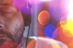 Halbes Gesichtsporträt des erwachsenen Mannes hörend Musik Lizenzfreie Stockfotografie