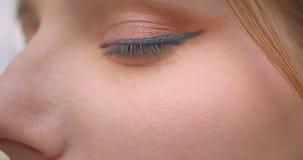 Halbes Gesichtsporträt des Nahaufnahmeprofils des jungen frohen kaukasischen weiblichen Gesichtes mit dem Auge, das Kamera mit de stock video