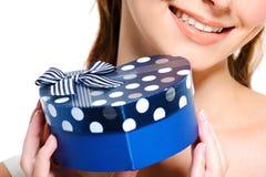 Halbes lächelndes Gesicht der Frau den blauen Kasten anhalten Stockbild
