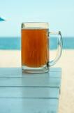 Halbes Liter auf Holztisch und dem Meer Lizenzfreies Stockfoto