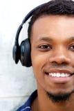 Halbes Porträt des lächelnden Mannes mit Kopfhörern hörend Musik Stockfoto