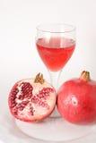 Halbes und vollständiges pomegrante mit Saft, Stockbild