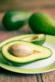 Halbierte Avocados auf altem Holztisch Stockfotos