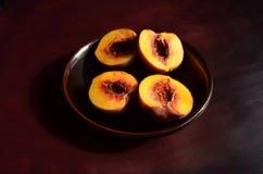 Halbierte Pfirsiche auf dunkelbrauner Platte und Oberfläche Stockbild