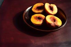 Halbierte Pfirsiche auf dunkelbrauner Platte und Oberfläche Lizenzfreies Stockbild