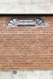 Halbkreisförmiges Fenster auf Backsteinmauer Lizenzfreies Stockfoto