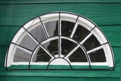 Halbkreisförmiges Fenster auf einer grünen Wand des Holzes Lizenzfreies Stockbild