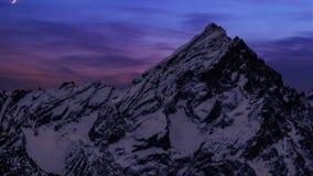 Halbmond, der unten schnell bei Sonnenuntergang über den Bergen bedeckt mit Schnee absteigt stock video footage