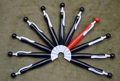 Halbrund von schwarzen Kugelschreibern mit einem roten  Stockfotos