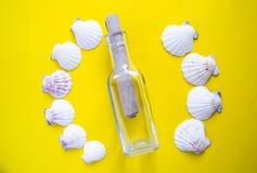 Halbrund von weißen Muscheln mit Mitteilung in einer Flasche auf gelbem Hintergrund lizenzfreies stockfoto