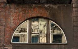 Halbrundes Fenster eine alte zerbröckelnde Backsteinmauer Lizenzfreies Stockfoto