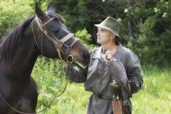 Halconero en ropa tradicional con el halcón y el caballo de peregrino Foto de archivo