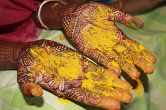 Haldi Ritual. A view of hands with mehendi having turmeric / haldi on their hands as a part of a traditional wedding ritual in India Stock Photos