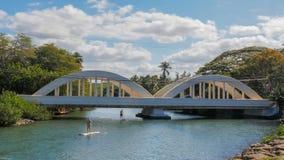 HALEIWA, DIE VEREINIGTEN STAATEN VON AMERIKA - 12. JANUAR 2015: Paddelinternatsschüler überschreiten unter die Brücke im haleiwa lizenzfreies stockbild