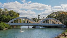 HALEIWA, UNITED STATES OF AMERICA - JANUARY 12 2015: paddle boarders pass under the bridge in haleiwa. Hawaii royalty free stock image