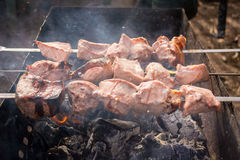 Half afgewerkte vleesvleespennen op de grill in rook Stock Foto's