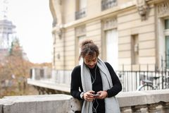Half African tourist listening to new songs in earphones with sm. Mulatto tourist raving with white in ear headphones and smartphone near Eiffel tower. Jocund Royalty Free Stock Photos